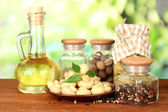 Composition of delicious marinated mushrooms, oil and spices on wooden table on bright background — Stock Photo