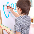 Little boy painting paints picture on easel — Stock Photo #24534287