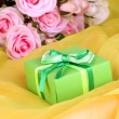 Beautiful gift on flowers background — Lizenzfreies Foto