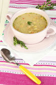 Nourishing soup in pink pan on wooden table close-up — Stock Photo