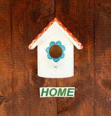 Decorative nesting box and sign on wooden background — Stock Photo