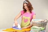 Young beautiful woman ironing clothes in room on grey background — 图库照片