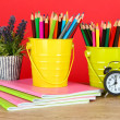 Colorful pencils in two pails with copybooks on table on red background — Stock Photo #24541539