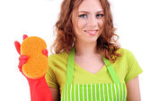Young woman wearing green apron and rubber gloves with sponge, isolated on white — Stock Photo