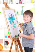 Little boy painting paints picture on easel — Stock Photo