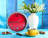 Cup coffee and clock on bright background — Stock Photo