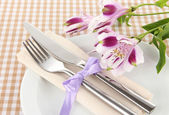 Festive dining table setting with flowers on checkered background — Stock Photo