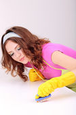 Young housewife cleaning up table at home — Stock Photo