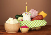 Easter basket: Conceptual photo of traditional easter food in wicker basket, on wooden table on color background — 图库照片