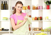 Woman wipes clean utensils in kitchen — Stock Photo