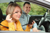 Couple sitting in the car (woman applying makeup) — Stock Photo