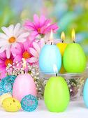 пасхальные свечи с цветами на ярком фоне — Стоковое фото