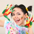 Стоковое фото: Young pretty painter with hands in paint, on gray background