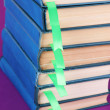 Stock Photo: Many books with bookmarks on purple background close-up