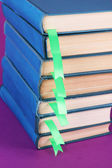 Many books with bookmarks on purple background close-up — Stock Photo