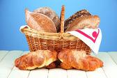 Ekmek ve rulolar, renkli arka plan üzerinde ahşap tablo hasır sepet kompozisyonu — Stok fotoğraf