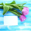 Beautiful bouquet of purple tulips and blank card on blue wooden background — Zdjęcie stockowe
