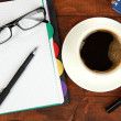 Stock Photo: Cup of coffee on worktable covered with documents close up