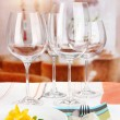 Stock Photo: Table setting with glasses for different drinks on table on room background