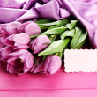 Beautiful bouquet of purple tulips on pink wooden background — Stock Photo #24595853