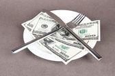 Money on plate on grey background — Stock Photo