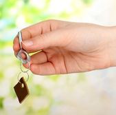 Key with leather trinket in hand on bright background — Stock Photo