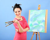 Beautiful young woman painter at work, on color background — Photo