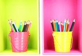 Lápis coloridos em baldes nas prateleiras — Fotografia Stock