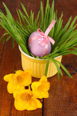 Easter eggs in bowl with grass on wooden table close up — Stock Photo