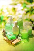 Botellas de cosméticos y jabón natural hecho a mano sobre fondo verde — Foto de Stock