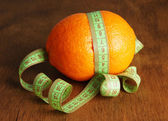 Orange with measuring tape, on wooden background — Stock Photo