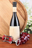 Composition of corkscrew and bottle of wine, grape, wooden barrel on wooden table on bright background — Stock Photo
