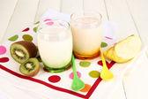 Deliciosos yogures con frutas en copas en primer plano de la mesa de madera — Foto de Stock