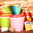 Set for painting: paint pots, brushes, paint-roller, palette of colors on stone wall background — Stock Photo #24610475