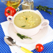 Nourishing soup in pink pon blue tablecloth close-up — Stock Photo #24614227
