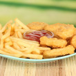 Fried chicken nuggets with french fries and sauce on table in park — Stok fotoğraf #24615777