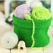 Colorful yarn for knitting in green basket on wooden table on window background — Stock Photo #24619581