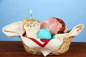 Easter basket: Conceptual photo of traditional easter food in wicker basket, on wooden table on color background — ストック写真