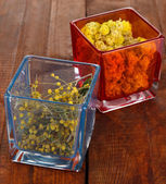 Dried herbs in glass containers on wooden table close-up — Stock Photo