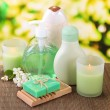 Cosmetics bottles and natural handmade soap on green background — Stock Photo #24622141
