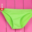 Womans panties hanging on a clothesline, on pink wooden background — Stock Photo #24622241