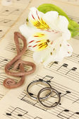 Treble clef, flower and wedding rings on musical background — Fotografia Stock