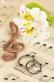 Treble clef, fiori e fedi nuziali su sfondo musica — Foto Stock