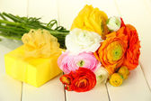 Ranunculus (persian buttercups) and gift, on white wooden background — Stock Photo