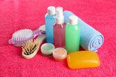 Hotel cosmetics kit on pink towel — Stock Photo