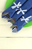 Fourchettes et couteaux, enveloppé dans des serviettes de papier bleu, sur fond de bois de couleur — Photo