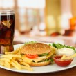 Tasty cheeseburger with fried potatoes and cold drink, on bright background — Stock Photo #24641735