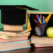 Books and magister cap against school board on wooden table on green background — Stock Photo