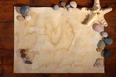 Oud papier, zeester en stenen op houten tafel — Stockfoto