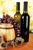 Composition of wine and grapes on wooden barrel on bright background — Stock Photo